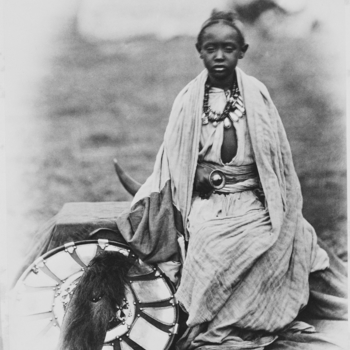 A young boy, Prince Alamayou, the only legitimate son of Tewodros II, sits on box covered with sheet; wears robes, large necklace & in right hand holds sword handle, in belt, with curved blade behind him; round shield leans upright to left.