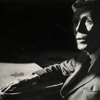 Framed photograph of a head and shoulder length portrait of Anthony Frederick Blunt (1907-83). He is seated at a desk gazing slightly upwards. A shadow falls across his face. A large book with a royal monogram is positioned on the desk in front of him. He