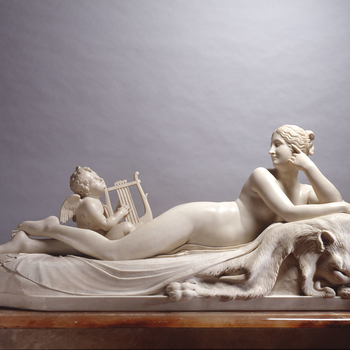 Rectangular statuary marble group of a naked nymph reclining full-length and cross-legged on a lion's pelt, with spring issuing water. Head of wavy hair gathered to her right, supported by left hand. A winged cherub seated at her feet plucks a lyre.<br />
