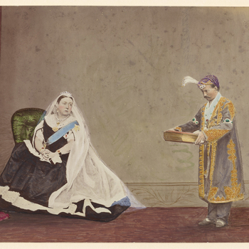 Composite photograph of Queen Victoria (1819-1901) who is seated on the left in a green chair wearing the Order of the Garter and a long lace head dress and, on the right, an Indian man (royal house of Benares?) who presents a large book or album to the Q