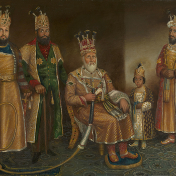 Five full-length figures in an interior with a richly patterened carpet; the Rajah sits, centre, holding the mouthpiece of a hookah pipe; two bearded males stand to the left; on the right stand a boy and another man; all richly clothed with jewels