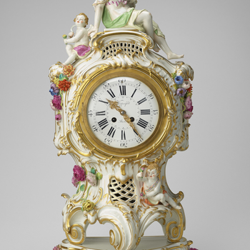 A mantel clock in a white porcelain serpentine roccoco style case surmounted by a veiled woman with a tamborine and putto. Below dial scrolled rocaille work with a putto to the left;  flowers in relief in coloured porcelain and a second putto hiding in th