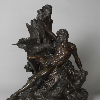 A bronze group of naked Prometheus seated and chained to a rock partially covered with draperies, with his right hand stretched, being pecked by an eagle and with a flaming torch lying below.  Prometheus, son of the titan Iapetus, stole fire from heaven