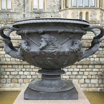 A bronze replica of the Warwick Vase, handles intertwined, fluted and leaf capped. The body with vine leaves and berries, scrolls and female and male heads in high relief. The base and top rim beaded and with tongue border. On rectangular speckled granite