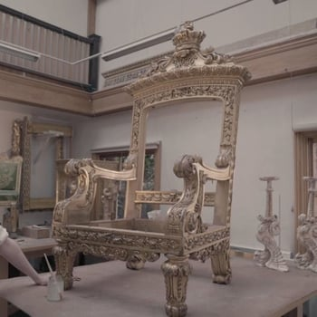 conservator standing with throne in the workshop