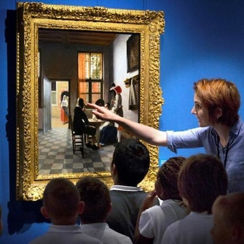 A group of children look closely at a painting by Vermeer with their teacher