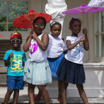 Group of 10 children with parasols in Buckingham Palace gardens