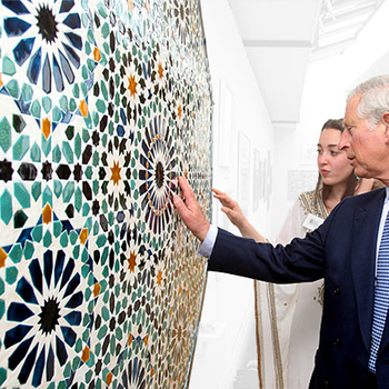 Prince Charles discusses an artwork with a student