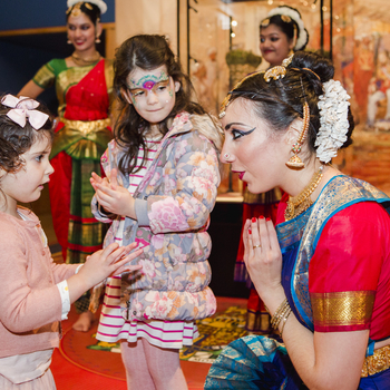 Children taking part in a dance lesson with a lady in traditional Indian dress