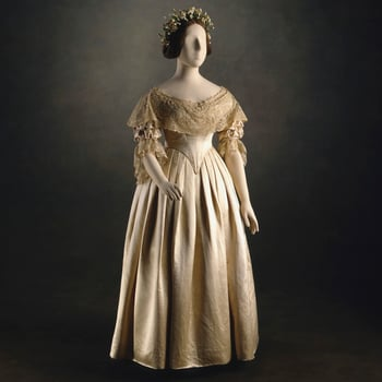Wedding dress ensemble of cream silk satin; comprising pointed boned bodice lined with silk, elbow length gathered sleeves; deep lace flounces at neck and sleeves and plain untrimmed skirt en suite, gathered into waist with unpressed pleats.<br> <br>Altho