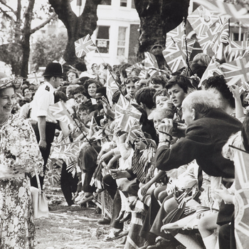 Photograph of HM Queen Elizabeth II (b.1926) visiting Highbury Fields during her Silver Jubilee tour of North London. She is walking to the left wearing a floral dress and holding a bouquet. There is a crowd of well wishers waving Union Jacks to the right