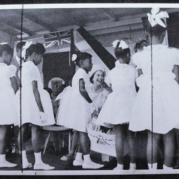 HM the Queen jokes with local children who stand with their backs to camera and wearing white dresses. The Queen attended the Harris Agricultural Show during her one day visit to Montserrat in the West Indies.