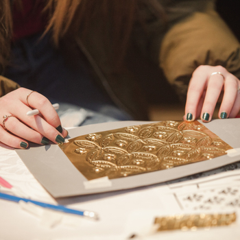 Child creating an Indian brooch with gold