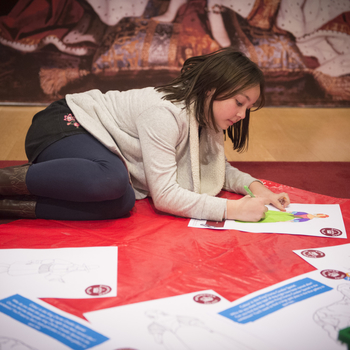 A girl is colouring a worksheet beneath a painting