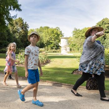 guide shows children around the garden area