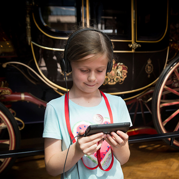 Child with multimedia guide at the Royal Mews