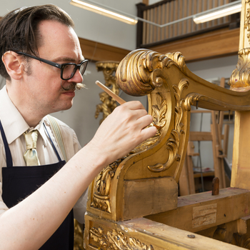 conservator working on gilt timber frame of throne