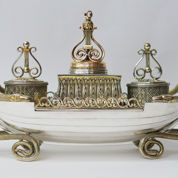 <p>A parcel gilt inkstand in the form of a rowing boat with planking and a central rib, with a pierced gallery at either side and entwined gilt snakes at either end, their coils forming supports for the boat. Fitted with a central rectangular well of cast