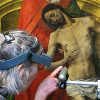 Conservator studying one of the Trinity Panels