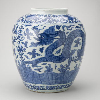 An ovoid-shaped Chinese Ming period porcelain jar painted in rich blue around the sides with two five-clawed dragons among clouds and with rocks and waves below.  Round the shoulder a stylised <em>shou</em> (long life character) seems to grow out of