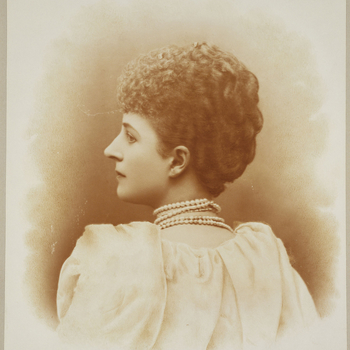Photograph of a head and shoulder length portrait of Queen Alexandra (1844-1925). Queen Alexandra is shown with her back facing the camera. She turns her head left, her face captured in profile. .She wears a dress with voluminous sleeves and a strings of