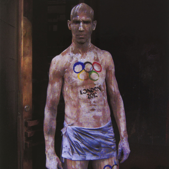Colour photograph of a three-quarter length portrait of a man standing, naked apart from a blue coloured piece of cloth tied around his hips. He faces the camera front on, staring down the camera lens. He is covered is white and black paint and