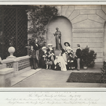Photograph of The Royal Family on the terrace at Osborne. From left to right:  Prince Alfred, Prince Albert, Princess Helena, Princess Alice, Prince Arthur, Queen Victoria holding Princess Beatrice, Princess Royal, Princess Louise, Prince Leopol
