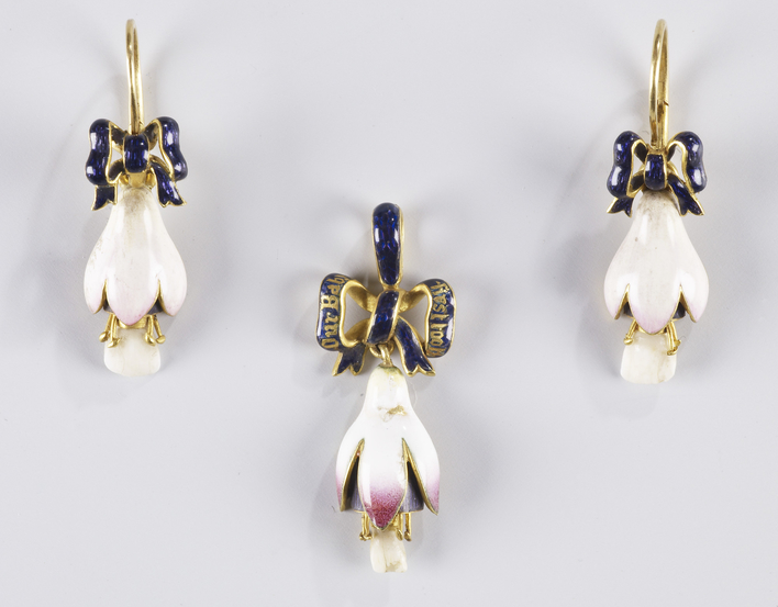 A pendant and a pair of gold mounted enamel earrings in the form of a fuscia flower set with milk teeth from Princess Beatrice (1857-1944), Queen Victoria's youngest child. These are suspended from an enamelled ribbon.The work of setting the teeth in the