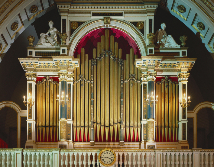 Three manual organ with a maplewood console in a painted and gilded case in the form of a triumphal arch flanked by life-size seated plaster figures and two gilded roundels of Handel.In 1818 Lincoln had installed an organ in Nash's newly built Music Room