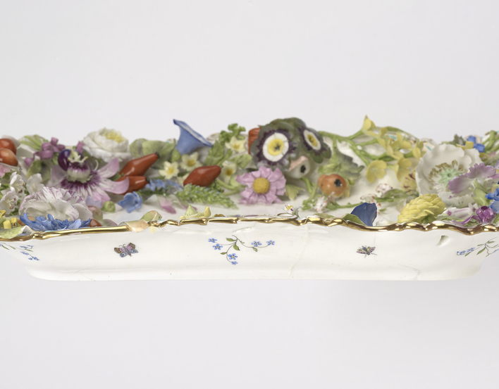 A rectangular porcelain tray painted in the centre with a crowned dated ribbon within a wreath. The border is encrusted with modelled coloured flowers (passion flowers, convolvulus, hips etc) and fruit. The bottom is painted with butterflies and floral sp