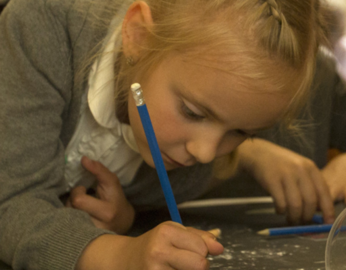 A girl leaning over paper and drawing with a pencil