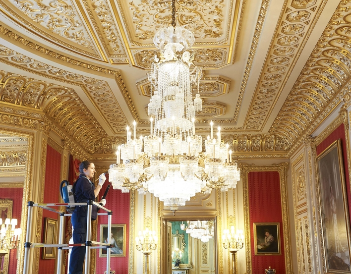 A chandelier is cleaned in the Crimson Drawing Room