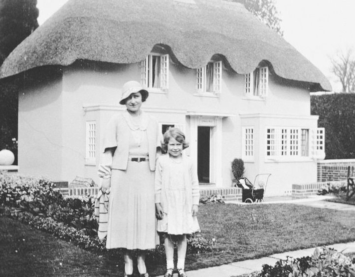 Young Princess Elizabeth and Queen Elizabeth in front of the Welsh Cottage