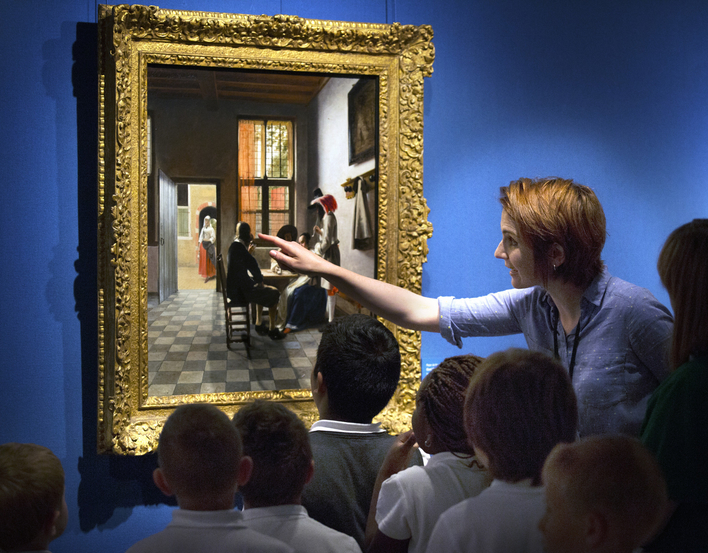 Small group of children with teacher looking closely at a painting on gallery wall