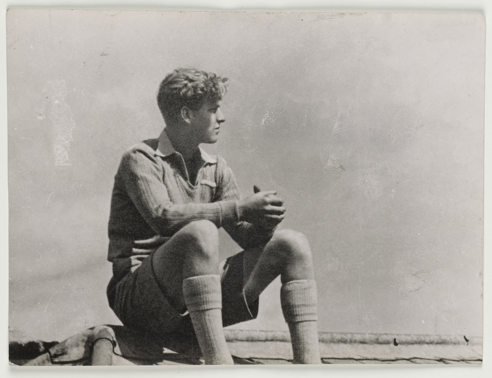 Full length, informal portrait of Prince Philip sitting on the roof of Gordonstoun School, facing right side profile. He wears school uniform. This image reproduced in Five Gold Rings, published in 2007.