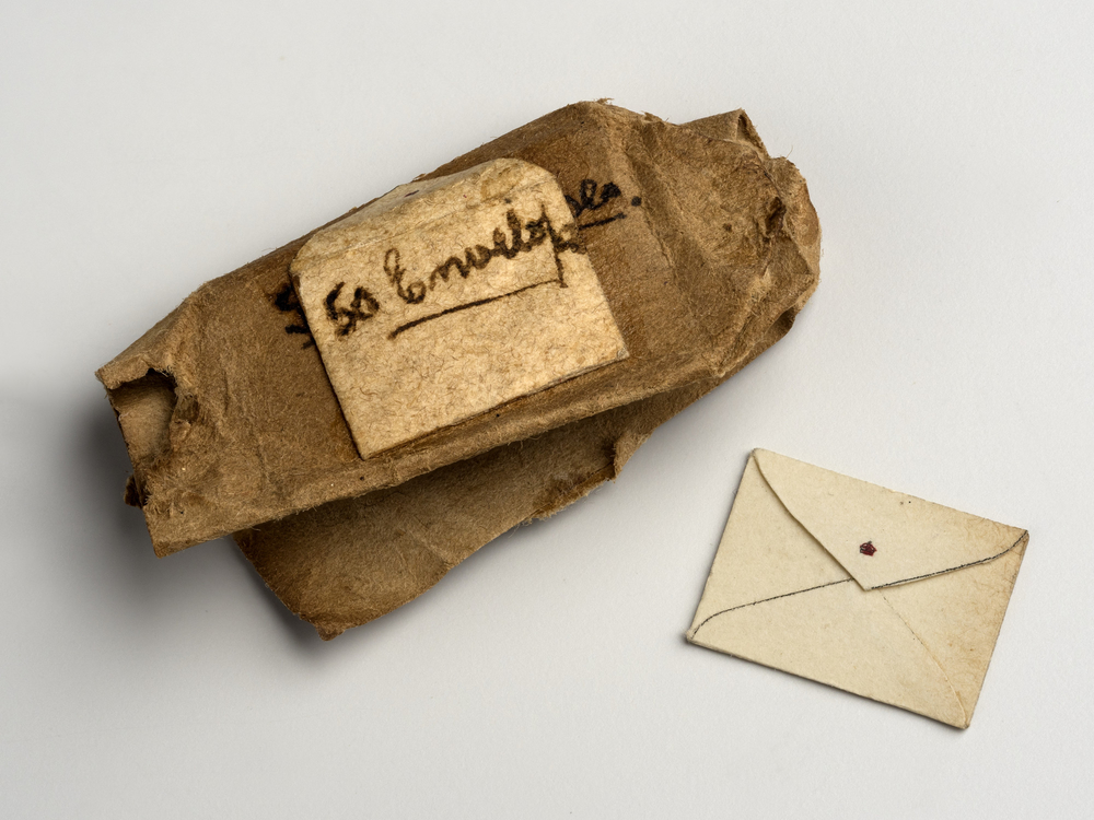 Miniature brown paper package containing envelopes with red crown on flap. Package has been opened. Some envelopes are loose.