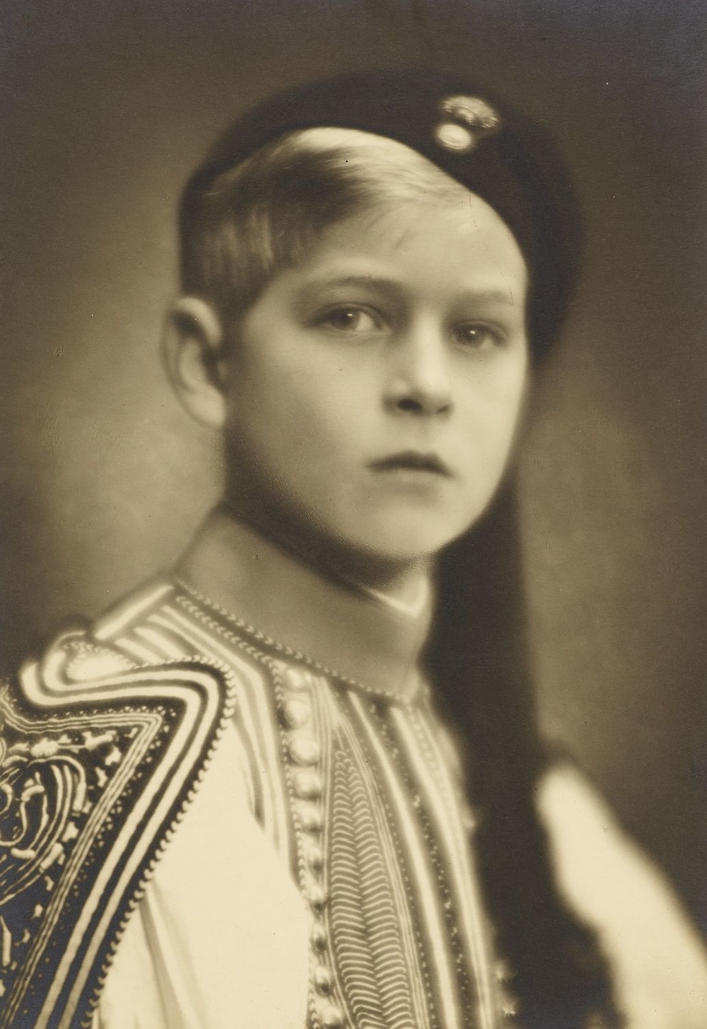 Photograph of a head and shoulders length portrait of Prince Philip of Greece, later HRH The Duke of Edinburgh, facing the viewer. He wears traditional Greek costume and hat.
