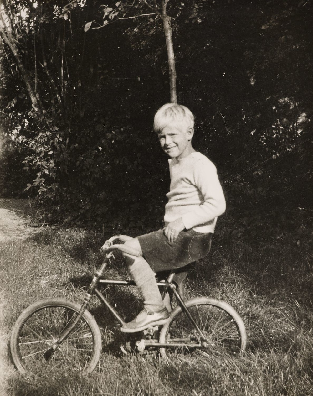 Photograph of Prince Philip of Greece, later HRH The Duke of Edinburgh, seated on a bicycle in left side profile. He faces the viewer, smiling.