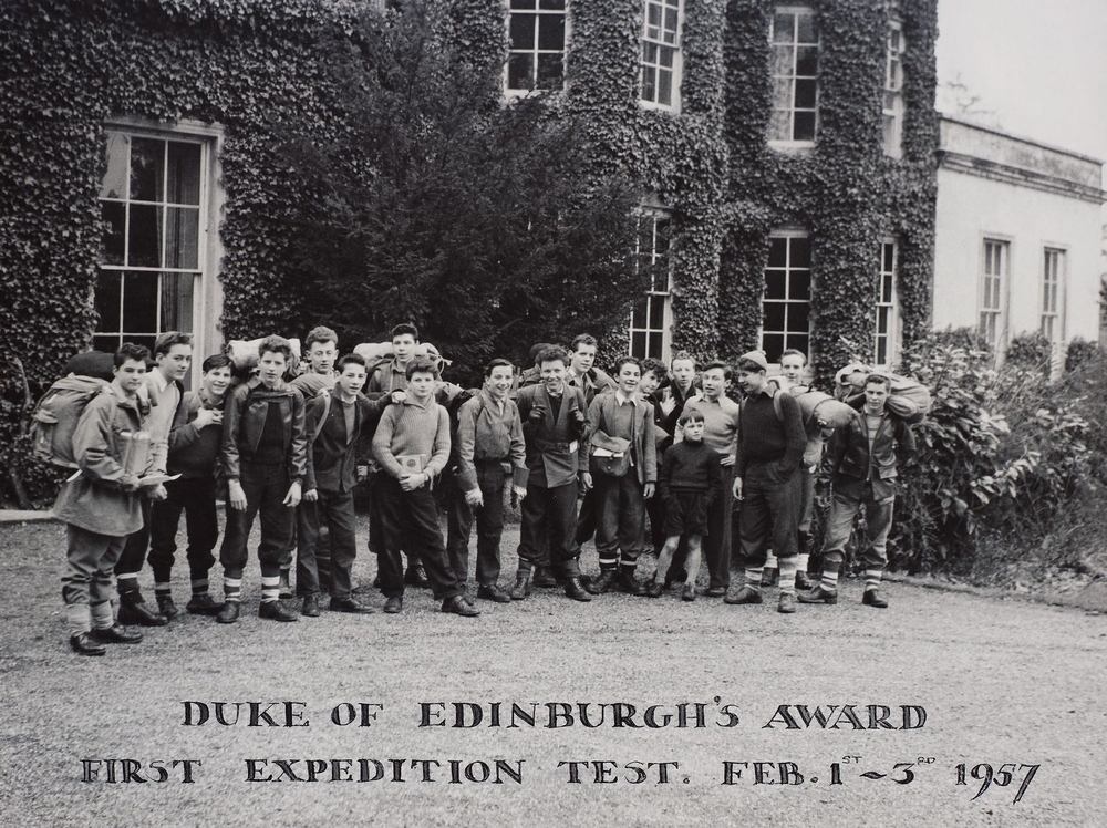 Photograph of a group of young boys with rucksacks and outdoor clothing pictured standing outside an ivy clad building who took part in the Duke of Edinburgh's Award First Expedition