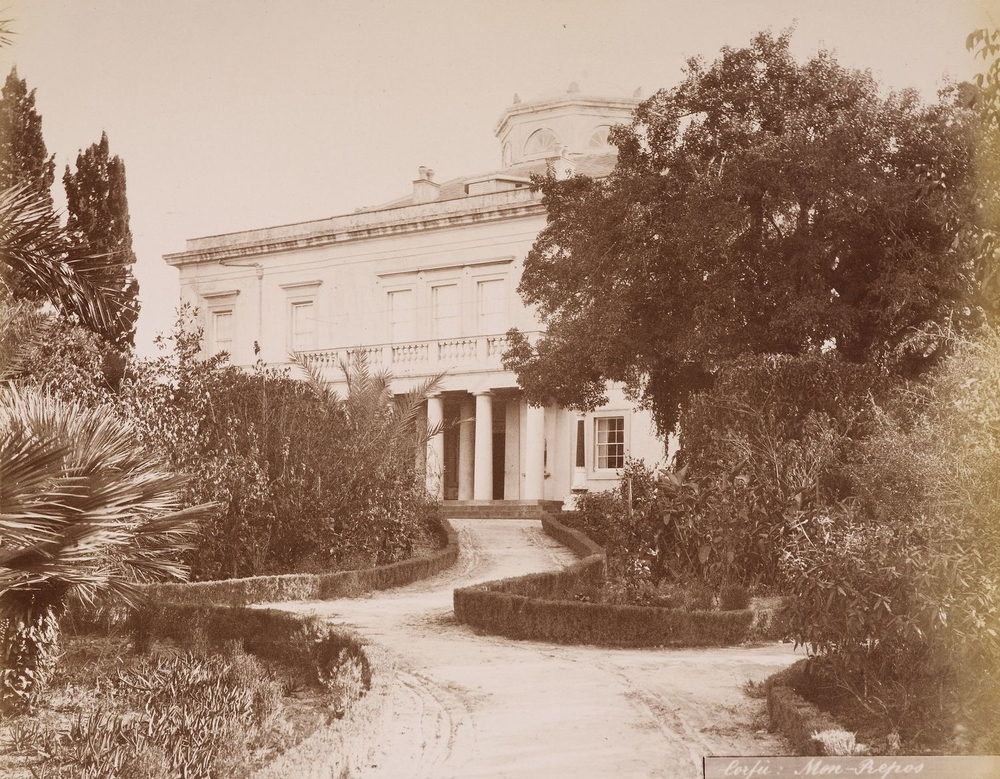 Photograph of Mon Repos villa on Corfu with a view up chicane in driveway, between low hedges separating it from beds of shrubs and trees. A neo-classical house stands at the end with a colonnaded porch.