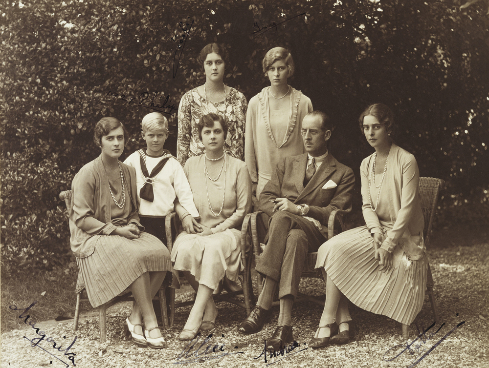 Photograph of a full length, formal group portrait of Prince Andrew of Greece (1882-1944) seated with Princess Andrew of Greece (1885-1969) who faces the viewer. They are pictured with their five children: Princess Margarita of Greece (1905-81), later Pri