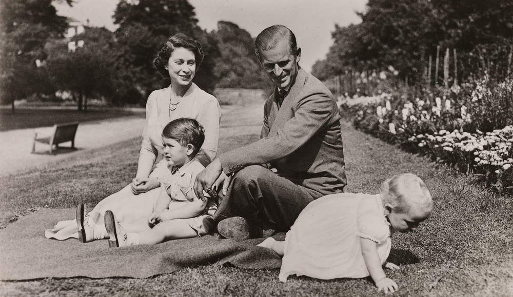 Photograph of HM The Queen (b. 1926) seated on the grass within the gardens of Clarence House. In front of her is seated HRH Prince Charles (b. 1948). HRH The Duke of Edinburgh (b. 1921) is seated on the Queen's left and looks at HRH Princess Anne (b. 195