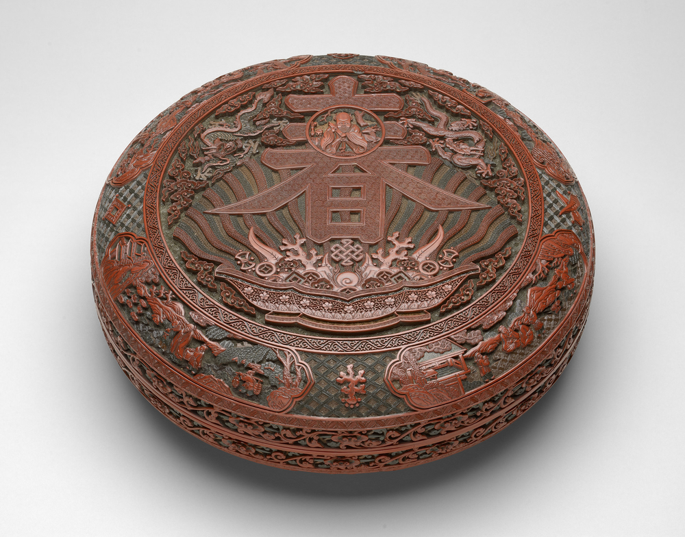 <p>Large Imperial shallow box, with rounded sides and flanged rim, the matching cover with almost flat top. With many layers of ochre-yellow, green and red lacquer applied over a wood base. Carved on the top, a circular panel within a &lsquo;meander scrol