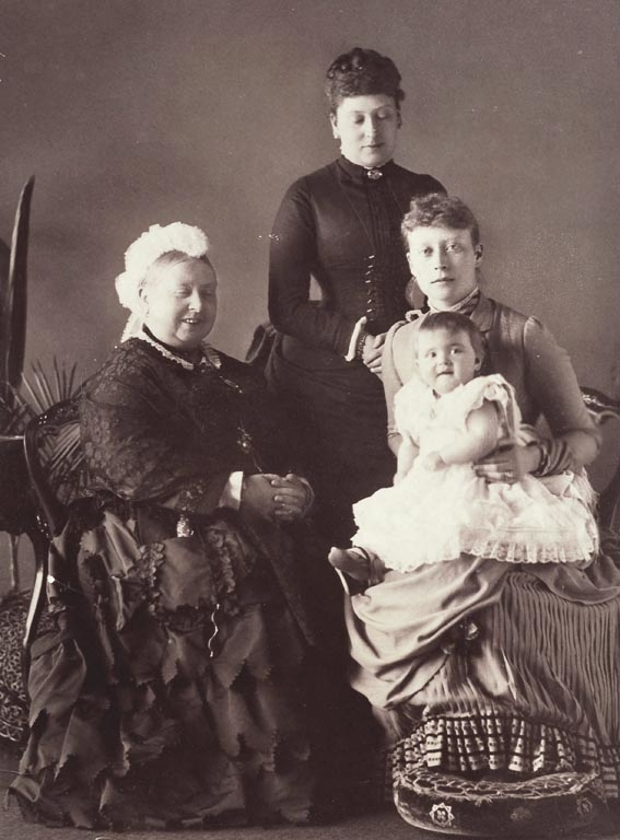 Photograph showing, from left to right: Queen Victoria, seated, smiling; Beatrice, Princess Henry of Battenberg, standing; Victoria, Princess Louis of Battenberg, seated, with Princess Alice of Battenberg on her lap.Despite her great sorrow at the dea
