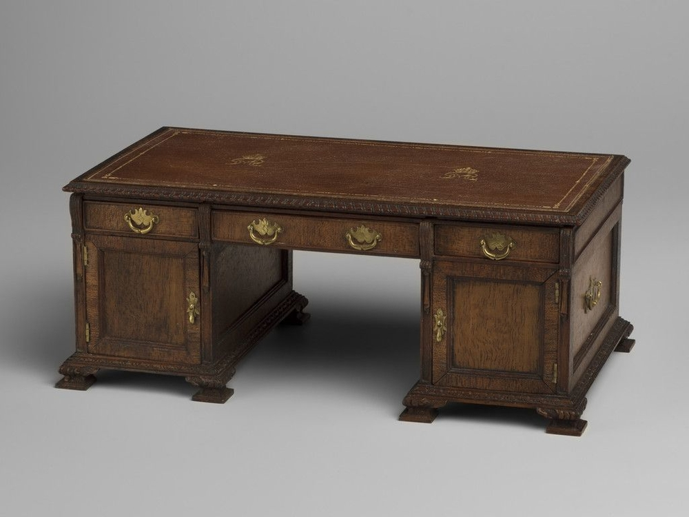Miniature walnut partners desk with tooled brown leather lined top with crowned GMR cypher.