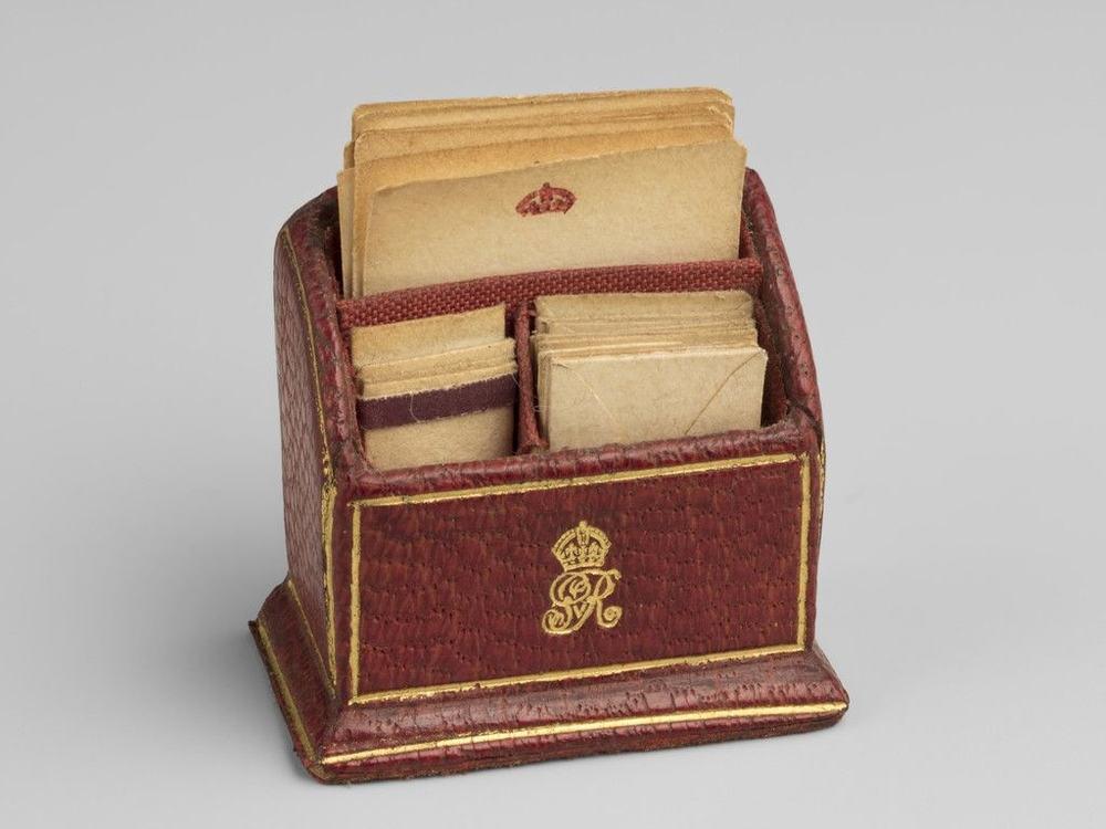 Miniature red leather letter rack divided into three compartments.
